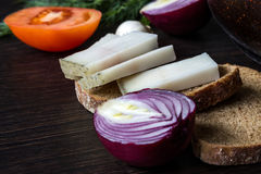 Ukrainian traditional food is lard salo with bread with red onions on the background of the tomato with garlic on  wooden table. Small depth of focus Stock Images