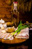 Ukrainian traditional food - salo. Sliced bacon with mustard, garlic, onion and vodka bottle. Ukrainian traditional food - salo. Sliced bacon with mustard Royalty Free Stock Photos