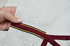 Ukrainian traditional needlecraft. A female hand holds the white homespun linen sleeve with handmade embroidery Stock Photography