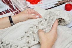 Ukrainian traditional needlecraft. Female hands hold the homespun linen sleeve embellished with cutwork embroidery Stock Photos