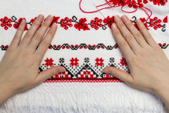 Ukrainian traditional pattern of characters. Woman embroiders national pattern red thread on a towel Stock Photography
