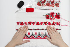 Ukrainian traditional pattern of characters. Woman embroiders national pattern red thread on a towel Stock Images