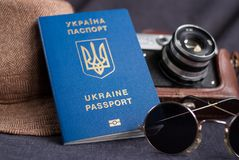 Ukrainian travel passport on gray background. sunglasses, hat. vintage camera on the background. EU visa free access. Shallow dept. Ukrainian travel passport on royalty free stock photos