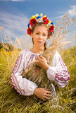 Ukrainian woman in embroidered shirt holding sheaf of wheat Stock Image