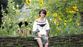 A Ukrainian woman sitting on the wicker fence and holding in the hand bouquet. Young Ukrainian woman sitting on the wicker fence and holding in the hand bouquet stock video footage