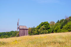 Ukrainian wooden windmill windmill stands near a forest in the f Royalty Free Stock Photos