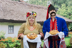 Ukrainians -  man and  woman, greeted guests with bread and salt. The Ukrainians - a man and a woman, dressed in national costumes on the background of the hut Stock Photography