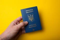 Ukrainische biometrische Passidentifikation in der Hand auf gelbem Hintergrund lizenzfreies stockfoto