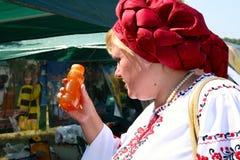 Ukrainische Frau im nationalen Kostüm wählt Honig Stockbild