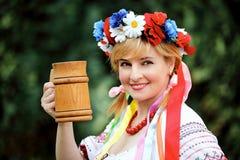 Ukrainische Frau mit einem hölzernen Becher Stockfotos
