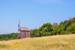 Ukrainische hölzerne Windmühlenwindmühle steht nahe einem Wald im f Lizenzfreie Stockfotos