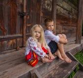 Ukrainische Kinder nähern sich altem Holzhaus Stockfotografie