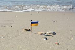 Ukrainische Miniaturflagge auf dem Strand des selektiven Fokus Schwarzen Meers Stockfotografie