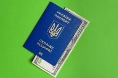 Ukrainischer biometrischer Pass mit hundert Dollarschein auf einem grünen Hintergrund Lizenzfreie Stockfotografie
