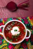 Ukrainischer traditioneller Borschtsch Russische vegetarische rote Suppe in der weißen Schüssel auf rotem hölzernem Hintergrund B stockbilder
