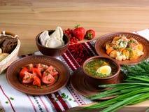 Ukrainisches Abendessen: Gemüsesuppe, Salat, vareniki, Gemüseeintopfgericht auf einem Holztisch Ukrainischer Lebensmittelhintergr Stockbild
