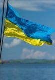 Ukrainisches Flaggenfliegen im Hintergrund von Himmel und von felsiger Küste O Lizenzfreie Stockbilder