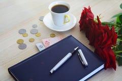 Ukrainisches Geld, ein Tagebuch mit einem Stift, Kaffee und Rosen Lizenzfreie Stockfotografie