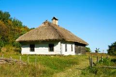 Ukrainisches ländliches Häuschen mit einem Strohdach Lizenzfreie Stockbilder