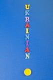 UKRAINISCHES Wort auf dem blauen Hintergrund verfasst von den hölzernen Buchstaben des bunten ABC-Alphabetblockes, Kopienraum für Lizenzfreies Stockbild