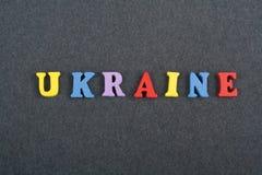 UKRAINISCHES Wort auf dem schwarzen Bretthintergrund verfasst von den hölzernen Buchstaben des bunten ABC-Alphabetblockes, Kopien Stockbilder
