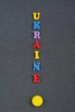 UKRAINISCHES Wort auf dem schwarzen Bretthintergrund verfasst von den hölzernen Buchstaben des bunten ABC-Alphabetblockes, Kopien Lizenzfreies Stockfoto