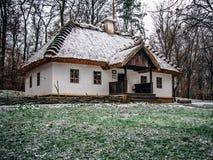 Ukrainsk bykoja med det halmtäckte taket fotografering för bildbyråer