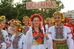 Ukrainsk grupp av flickor i traditionella dräkter på den internationella folklorefestivalen för barn och guld- fisk för ungdom Royaltyfri Bild