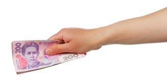 Ukrainsk hryvnia för pengar 200 i den kvinnliga handen som isoleras på vit Fotografering för Bildbyråer
