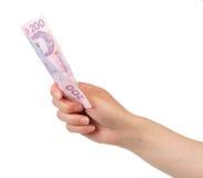 Ukrainsk hryvnia för pengar 200 i den kvinnliga handen som isoleras på vit Arkivfoton