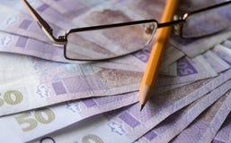 Ukrainsk hryvnia med blyertspennan och exponeringsglas Ukrainskt pengarfoto Royaltyfria Bilder