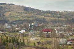 Ukrainsk by i dalen av Carpathian berg. Arkivfoton