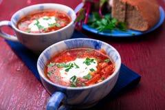 Ukrainsk traditionell borsch Rysk vegetarisk röd soppa i blått bowlar på röd träbakgrund Borscht borshch med beta Två royaltyfria foton