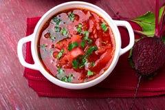 Ukrainsk traditionell borsch Rysk vegetarisk röd soppa i den vita bunken på röd träbakgrund Top beskådar Borscht borshchintellige royaltyfri foto