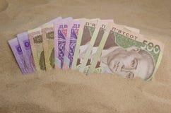 Ukrainska pengar i sand Arkivfoton