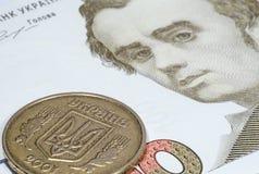 Ukrainskt mynt på en sedel av hundra hryvnias arkivfoto