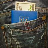 Ukrainskt pass och kontant in jeansfack Royaltyfri Bild