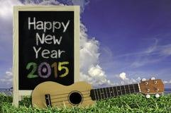 Ukulélé avec le ciel bleu et le texte du tableau noir 2015 sur l'herbe Photo libre de droits