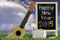Ukulélé avec le ciel bleu et le texte du tableau noir 2015 sur l'herbe Images libres de droits