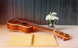 Ukulélé et carnet et fleur vides pour le concept de musique d'amour Images libres de droits