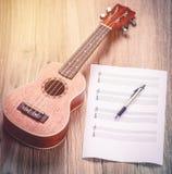 Ukulélé et notes de papier musicales Image stock