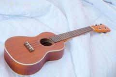 Ukulélé sur le lit blanc, instrument de musique images libres de droits