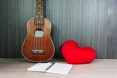 ukulele και κόκκινη καρδιά με το κενό βιβλίο σημειώσεων με το μολύβι στοκ φωτογραφία