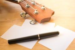 Ukulele auf hölzernem Schreibtisch, warmer Ton, nahes hohes der Ukulele, Musik conc Stockfoto