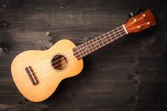 Ukulele on black wooden background. Acoustic music instruments. T stock images