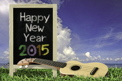 Ukulele with blue sky and Blackboard 2015 text on the grass. Stock Photos