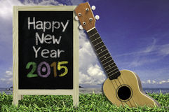 Ukulele with blue sky and Blackboard 2015 text on the grass. Stock Images