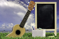 Ukulele with blue sky and Blank Blackboard on green grass. Royalty Free Stock Images