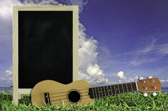 Ukulele with blue sky and Blank Blackboard on green grass. Stock Photo