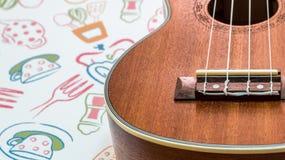 Ukulele. Close up of ukulele on tablemat Royalty Free Stock Photo